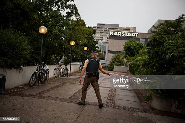 A police officer secures an area outside of OlympiaEinkaufszentrum shopping center after a shooting in Munich Germany on Friday July 22 2016 German...