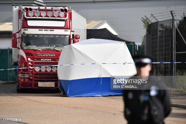Police officer secures the cordon at at the scene where a lorry, believed to have originated from Bulgaria, and found to be containing 39 dead...