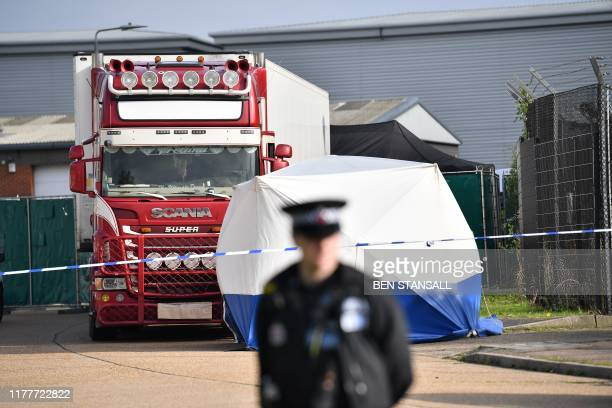 A police officer secures the cordon at at the scene where a lorry believed to have originated from Bulgaria and found to be containing 39 dead bodies...