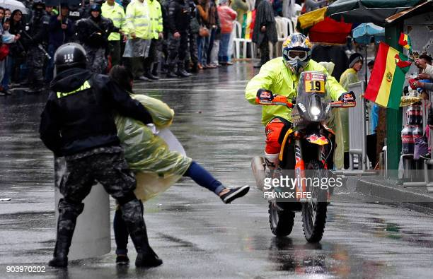 TOPSHOT Police officer seizes a demonstrator in front France's Antoine Meo at the end of Stage 6 of the 2018 Dakar Rally between Arequipa and La Paz...