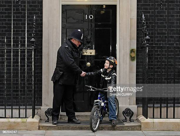 A police officer shakes hands with sevenyearold Charlie Simpson outside 10 Downing Street in central London on January 27 2010 Charlie set out to...