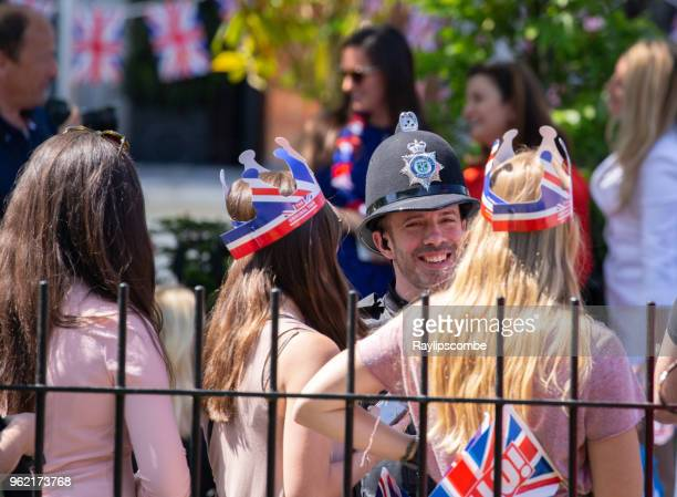 police officer shares a joke with the gathering crowds of people at windsor great park to celebrate the marriage of meghan markle and prince harry - meghan stock photos and pictures
