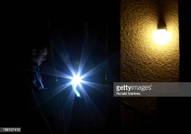 A police officer shines a flashlight outside an apartment building where seven people were found dead at Lincoln Vineyard Apartment Homes on December...