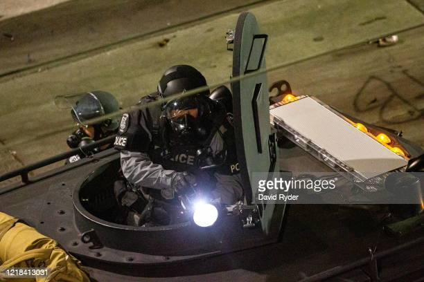 A police officer shines a light from the top of an armored vehicle as demonstrators clash with police near the Seattle Police Departments East...