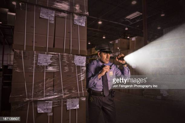 Police officer shining flashlight in warehouse