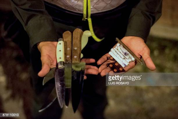 A police officer shows in his hands some knives and marijuana cigarettes decomissioned during a police security operation in the Vallado neighborhood...