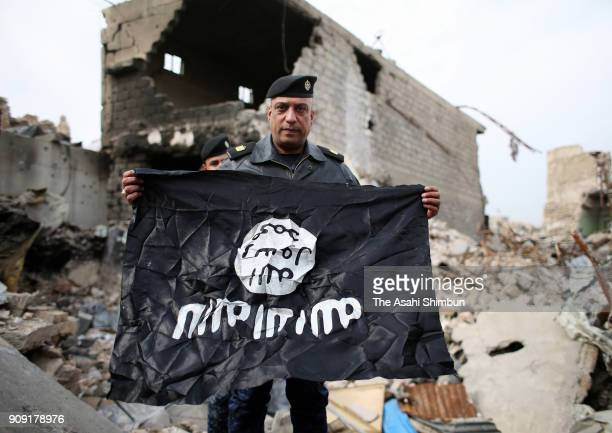 A police officer shows the Islamic State flag picked up in the old town on January 14 2018 in Mosul Iraq