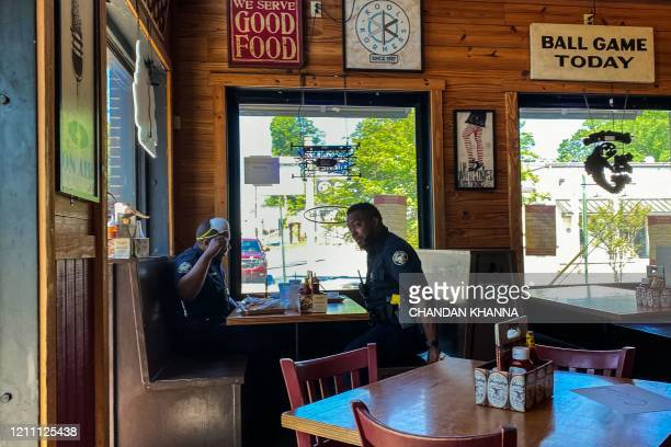 Police officer siting at a table, eats at Moe's Original BBQ restaurant amid the coronavirus pandemic in Atlanta, Georgia on April 27, 2020. - Some...
