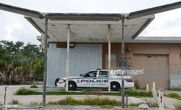 A police officer sits in his patrol car at an abandoned building ahead of the Republican National Convention in Tampa Florida on August 26 2012 Due...