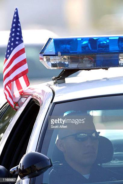 A police officer sits outside the CBS studios as celebrities arrive for 'America A Tribute To Heroes' telethon September 21 2001 in Los Angeles CA...