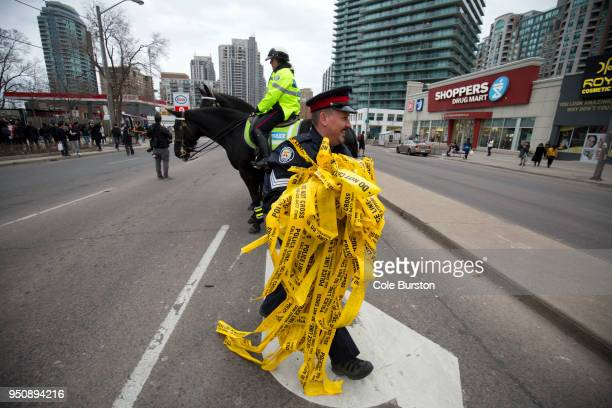 A police officer smiles as he walks off with used police tape after the partial opening of Yonge Street at Finch Avenue April 24 2016 in Toronto...