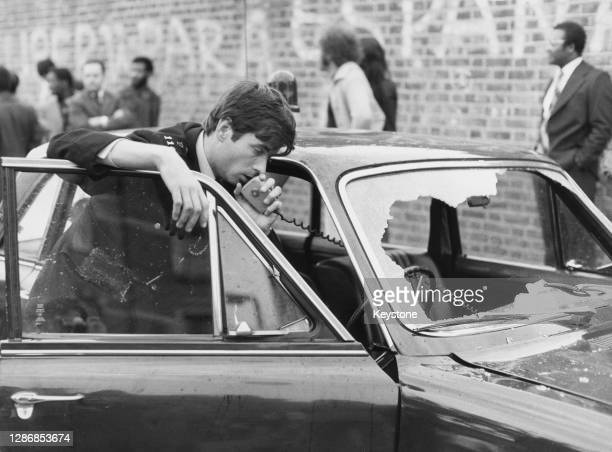 Police officer speaks into the handset of the radio in his car, which has its windscreen smashed in, with people on the street in the background as...