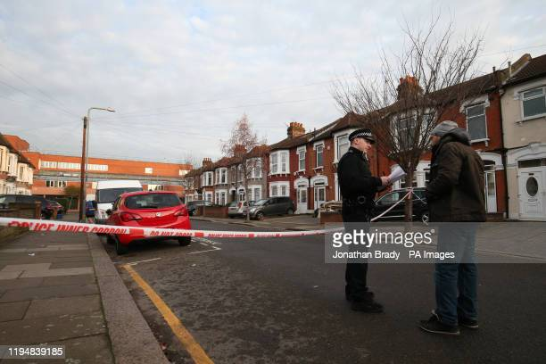 Police officer speaks to a man at the scene on Elmstead Road in Seven Kings, Ilford, east London, where three people died after being stabbed Sunday...
