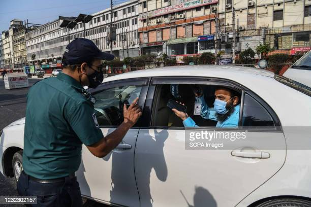 Police officer speaks to a man in a car at a checkpoint. Police checkpoints are set up in various places in the capital to stop the unnecessary...