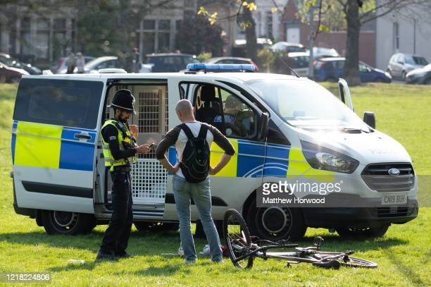A police officer speaks to a man on Roath Recreation Ground on April 11 2020 in Cardiff United Kingdom Police have stepped up patrols to prevent...