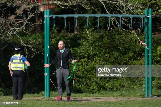 Police officer speaks to a man who was using exercise equipment at Roath recreation ground on April 11, 2020 in Cardiff, United Kingdom. Police have...