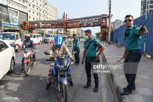 Police officer speaks to a motorcyclist at a checkpoint in Banani. Police checkpoints are set up in various places in the capital to stop the...