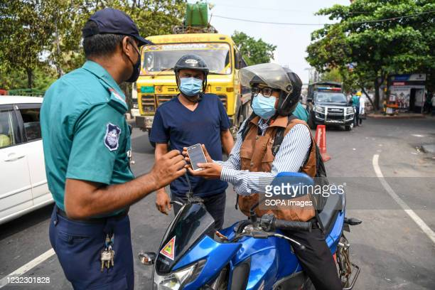 Police officer speaks to a motorcyclist at a checkpoint in Dhanmondi. Police checkpoints are set up in various places in the capital to stop the...