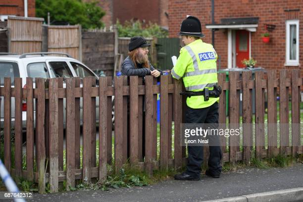 A police officer speaks to a neighbour as forensic teams search the former home of terrorist Salman Abedi on May 24 2017 in Manchester England An...