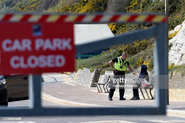 Police officer speaks to a person seated on a bench at Boscombe beach on April 13, 2020 in Bournemouth, United Kingdom. The Coronavirus pandemic has...