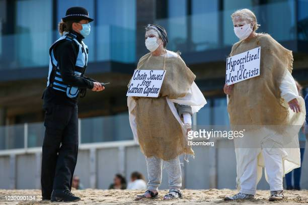 Police officer speaks to protesters dressed in white and hessian sacks as they demonstrate against tree felling at the Carbis Bay Hotel development...