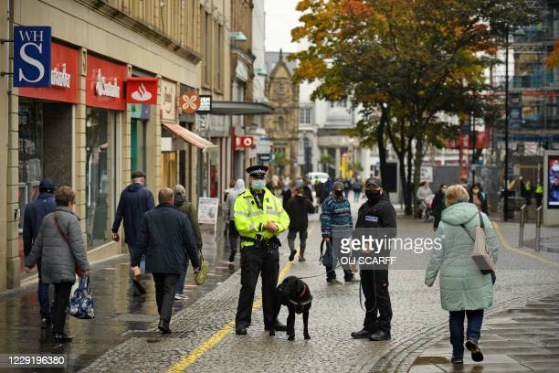 Police officer speaks with a dog handler in the shopping district in central Sheffield, south Yorkshire on October 21 prior to further lockdown...