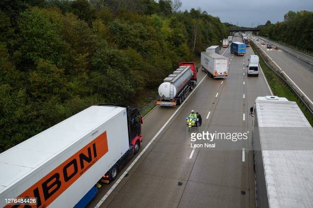 A police officer speaks with a driver as he marshalls the heavy goods vehicles on the M20 motorway as part of the Operation Stack traffic control...