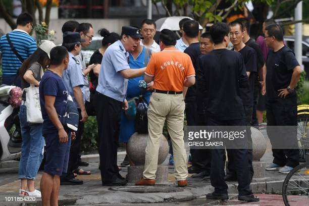 A police officer speaks with a petitioner as security personnel look on opposite China's Banking Regulatory Commission in Beijing on August 6 2018...