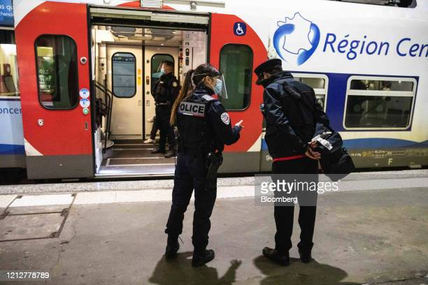 A police officer speaks with a railway worker beside a regional train at Gare Montparnasse railway station in Paris France on Tuesday May 12 2020 The...