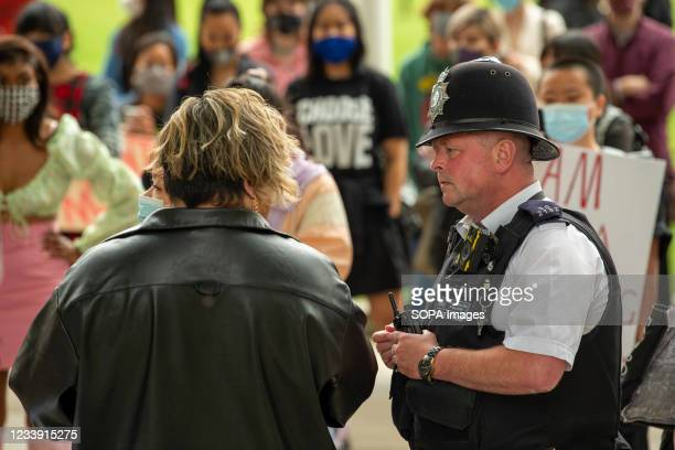Police officer speaks with an organizer of the Stop Asian Hate protest at Parliament Square in London. Anti-Asian violence and abuse has escalated...