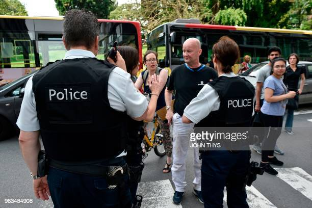 TOPSHOT A police officer speaks with parents of children at a nearby high school in the eastern Belgian city of Liege on May 29 after a gunman killed...