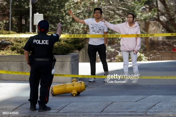 A police officer speaks with pedestrians trying to cross Yonge St at near Finch Ave after a van plowed into pedestrians on April 23 2018 in Toronto...
