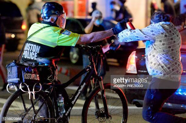 A police officer sprays a protester with pepper spray during a demonstration over the death of George Floyd an unarmed black man who died in...