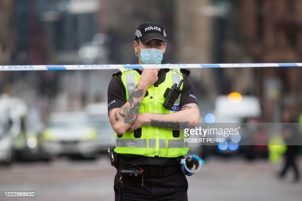 Police officer staffs a cordon as emergency services attend the scene of a fatal stabbing incident at the Park Inn Hotel in central Glasgow on June...