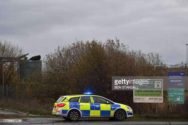 Police officer staffs a cordon with a damaged silo seen in the background at a waste water treatment plant in Avonmouth, near Bristol in southwest...