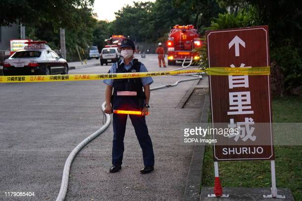 A police officer standing behind the limit line at the Shurijo castle a UNESCO World Heritage site Fire broke out around midnight and burned down the...