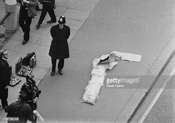 A police officer standing guard over a large stock of explosives on the pavement outside New Scotland Yard London after a car bombing by the...