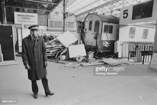 A police officer standing near the wreckage of 'Hastings 6B DEMU 1032' train which crashed on Charing Cross Station concourse London UK 11th January...