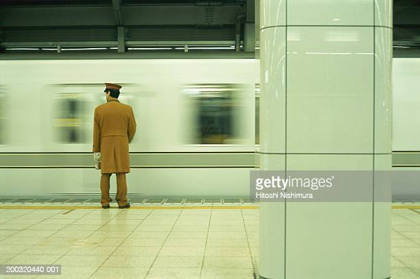 Police officer standing on railway platform, rear view