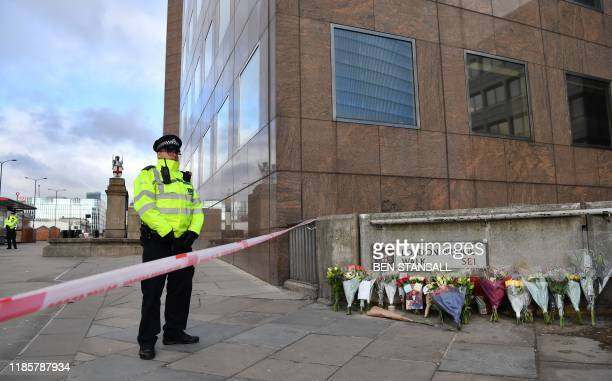 A police officer stands at a cordon beside floral tributes left close to London Bridge in the City of London on December 1 following the November 29...