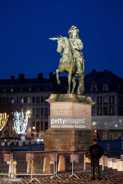 A police officer stands at dawn next to a statue of French monarch Louis XIV as 'Yellow Vest' protestors plan to demonstrate in front of the Chateau...