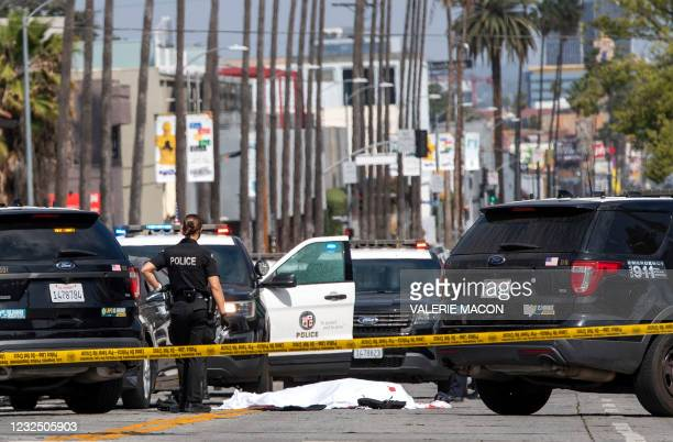 Police officer stands at the corner of Fairfax Avenue and Sunset Boulevard where a body covered in a white sheet lies on the pavement in Los Angeles...