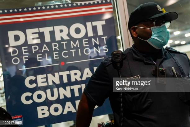 Police officer stands at the entrance to the Detroit Department of Elections Central Counting Board of Voting absentee ballot counting center at TCF...