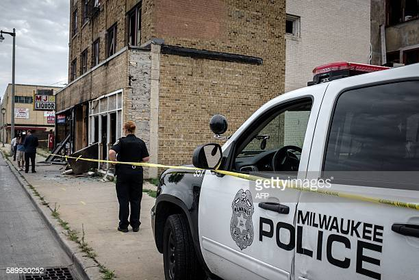 A police officer stands before the remains of a bar in Milwaukee Wisconsin August 15 2016 after police in the Midwestern city faced off with...