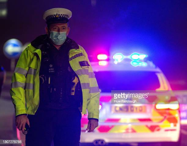 Police officer stands behind his vehicle as the blue lights flash during a roadside check on December 20, 2020 in Ystrad Mynach, Wales. As key...