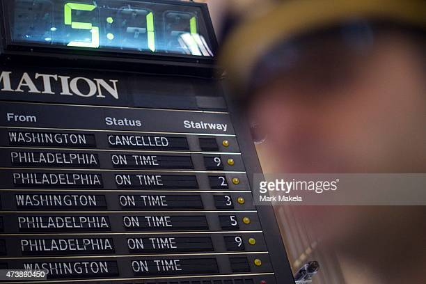 A police officer stands below an information board announcing the morning train departures as Amtrak resumes northbound service from 30th Street...