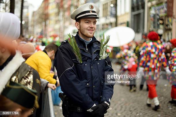 Police officer stands between Carnival revellers during a carnival parade called 'Schull un Veedelszoech' as part of the carnival season on February...