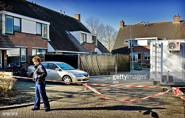 Police officer stands by a cordon erected around a house which was the site of a multiple killing in Zierikzee in Zeeland, early on March 7, 2010....