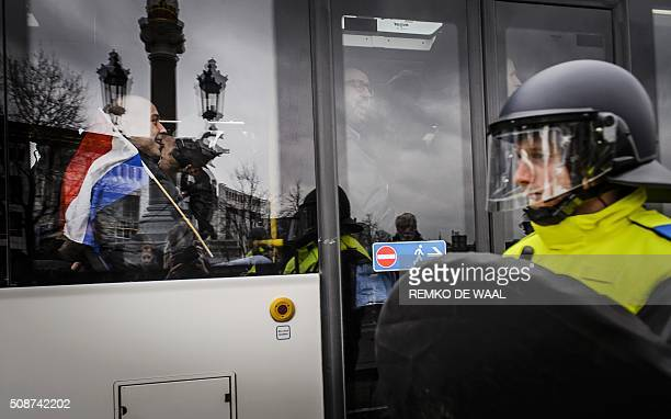 A police officer stands by as members of Pegida leave in a bus after holding a demonstration in central Amsterdam on February 6 2016 AntiIslamic...