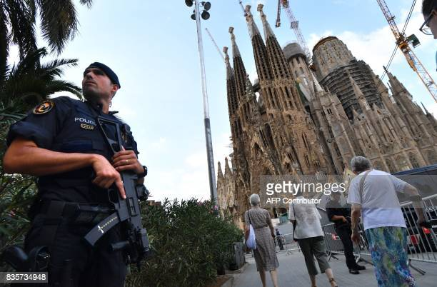 TOPSHOT A police officer stands by the Sagrada Familia basilica in Barcelona on August 20 before a mass to commemorate victims of two devastating...